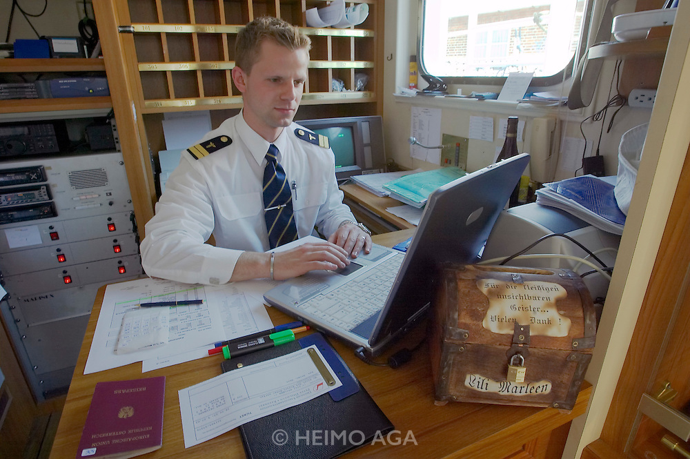 "The ""Lili Marleen"" (luxurious sailing ship of Deilmann Cruises) at the harbour. The purser keeping his books up-to-date with his Laptop."