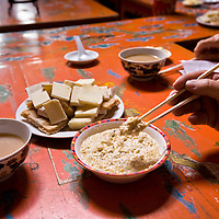A traditional food offering of very dry cheese (Eetsgii), milk tea (Nai Cha) and a sweet yogurt dip with toasted millet and sugar (Uremtei Khool) is alway offered at village yurts and homes in Inner Mongolia, northeastern China.