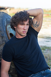 good looking  young man with curly brown hair wearing a black tee shirt and jeans outdoors leaning against a large tire