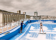 Royal Caribbean, Harmony of the Seas, surfing in one of the two flowrider simulator. FlowRider – the surf's always up at the two FlowRider surf simulators, which pump 34,000 gallons of water per minute and enable guests to stand-up surf or boogie board. Located at the aft of the ship, the FlowRiders afford spectacular views of the wide open ocean ahead.