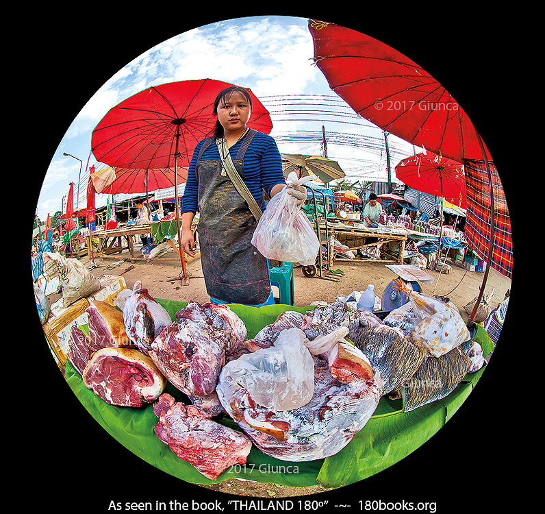 A woman sells frozen wild boar meat at a Hill Tribe Market in Tak, Thailand.