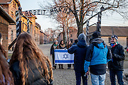"A group of a students with a jewish flag are doing photographs under the sign ""Arbeit macht frei"" at the entrance to the Auschwitz Nazi concentration camp. It is estimated that between 1.1 and 1.5 million Jews, Poles, Roma and others were killed in Auschwitz during the Holocaust in between 1940-1945."