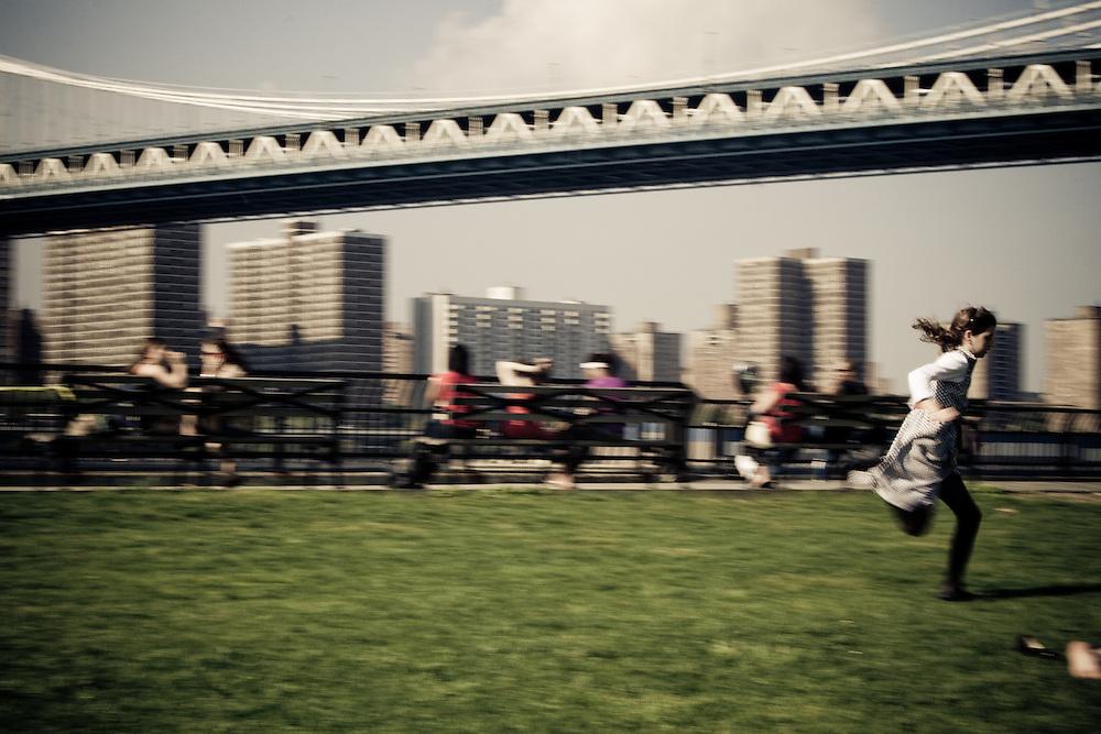 A girl runs through Empire-Fulton Ferry State Park near Manhattan Bridge in Brooklyn, NY.