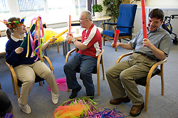 Group of service users with learning disabilities using rhythm sticks during a music session,