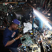 Electronic waste export to Nigeria...Alaba International Market, one of the largest markets for electronic goods in West Africa.  New and old - and a lot of non-working electronic goods such as TVs and computers come in to the market via Lagos harbour from the US, Western Europe and China...Julius Paul, a TV repair man at Alaba Market.  His speciality is Sharp televisons...The shipment - TV-set originally delivered to municipality-run collecting point in UK for discarded electronic products - was tracked and monitored by Greenpeace using a combination of GPS (Global Positioning System using satellites), GSM (positioning using data from mobile networks to triangulate approximate positions) and an onboard radiofrequency transmitter (used for making triangulations in combination with handheld directional receivers used by team on ground) is placed inside the TV-set.  The TV arrived in Lagos in container no 4629416.