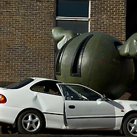 Car squashed by a giant metal ball exhibit at Petticoat Lane market, London<br />
