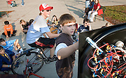 Minford Middle School student Drew Smith (center) adjusts the controls as fellow student Levi Munn pedals a bicycle to generate energy to run small household appliances during a demonstration at  Ohio University's Energy Fair on Wednesday, 10/4/06.