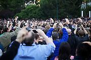 Many people taking photos surrounding something interesting.