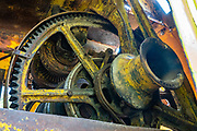 Old yellow gears at Fort Nelson Heritage Museum, 5553 Alaska Highway, Fort Nelson, British Columbia, Canada. This quirky museum features a highway construction display, pioneer artifacts, trapper's cabin, vintage autos & machinery, a white moose, and more.