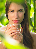 Portrait of young woman in corn field with drinking glass