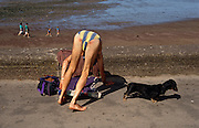 An unrecognisable bather wearing a stripy costume bends over awkwardly to adjust his towel on the promenade pavement (sidewalk) at Minehead, Devon. The man's reddened posterior is pointed towards the viewer and his dachshund (sausage) pet dog stands still looking away to the right, towards unseen interest. A family of four stroll along the sandy beach during low tide. It is a hot afternoon but we only see a quiet scene at this busy resort.