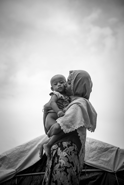 Shamsur Nahar, age 25, kisses her one-year-old daughter Yasmin Ara. They are from Myanmar's Rakhine State but now living in Kutupalong refugee camp in Bangladesh. (October 29, 2017)