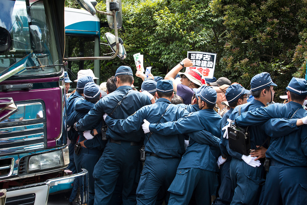 OKINAWA, JAPAN - SEPTEMBER 14 : Anti U.S base protesters is seen being guarded by police after they were removed from the road blocking to protest against the construction of helipads in front of the gate of U.S. military's Northern Training Area in the village of Higashi, Takae, Okinawa Prefecture, Japan on September 14, 2016. The Japanese government is allowing the use of its own Japan Air Self-Defense Force military helicopters Boeing CH-47 to get construction heavy equipments past the protesters on Tuesday, September 13 in order to speed up completion of six new helipads to be use by U.S Military.  (Photo by Richard Atrero de Guzman/NURPhoto)