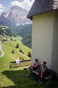 Walkers rest in the shade at the church of Santa Berbura, founded and built by iron miners in 1490, in the Dolomites near La Val in Alta Badia, south Tyrol, Italy.