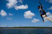 Boy balancing sailboat, dhow, off Lamu Island, Kenya, Africa