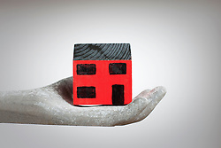Hand holding model of house (Credit Image: © Image Source/Ian Nolan/Image Source/ZUMAPRESS.com)