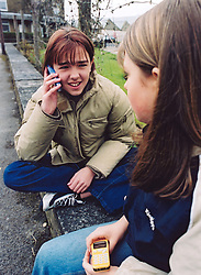 Two teenage girls sitting on a wall using mobile phones, UK