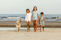 Two sisters and their little brother walk on the beach with the family dog.