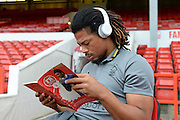 Nottingham Forest midfielder Hildeberto Pereira (17) reads the match program and listens to music with his Beats headphones ahead of the EFL Sky Bet Championship match between Nottingham Forest and Fulham at the City Ground, Nottingham, England on 27 September 2016. Photo by Jon Hobley.