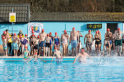 © Licensed to London News Pictures. 28/01/2017. London, UK. Swimmers enter the 'Jump in for Crisis' race at the 7th UK Cold Water Swimming Championships, taking place at Tooting Bec Lido. Ice in the Lido has only recently thawed following freezing temperatures in London over the past week. Temperatures in the pool today at 1 degree celsius. Photo credit : Tom Nicholson/LNP