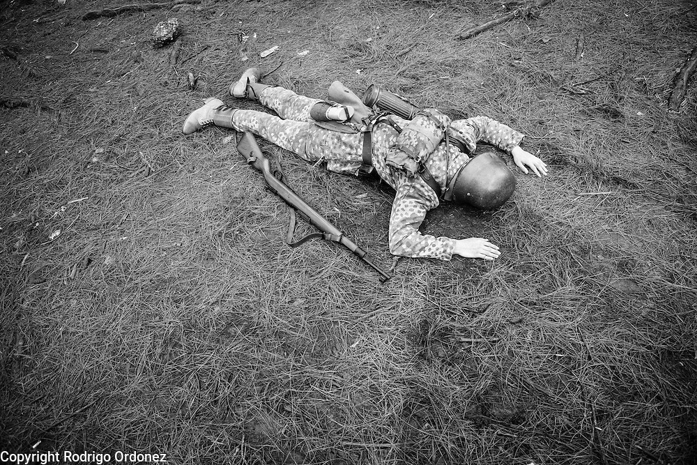 An Indonesian man dressed up as a German Waffen-SS soldier lies on the ground pretending to be dead during a gathering of re-enactment enthusiasts in Cibubur, East Jakarta, Indonesia.<br /> Members of the 'Niederlande Kampfgruppe' group meet regularly to re-enact battles wearing Nazi Germany military uniforms and produce their own photos and videos. They claim that they do not do this because they identify ideologically with the Nazis, but because they are interested in World War II and military history. According to them, there is historical evidence that at least one Indonesian person was part of the 'Freiwilligen Legion Niederlande', the Dutch arm of the Waffen-SS, during World War II. Similar re-enactment groups exist in several cities across Indonesia, using the uniforms of Dutch, German and Japanese troops.