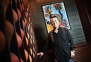 World-renowned Japanese chef Nobu Matsuhisa poses in front of a painting by the father of his business partner, American actor Robert de Niro, at their restaurant in central Tokyo, Japan.