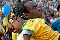 Father holding sleeping  child at West Indian Jamaican family day at Crystal Palace Park South London