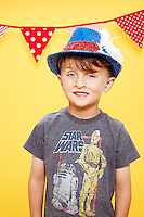 portriat of 7 year old boy wearing red white and blue fedora hat against yellow seamless.<br /> Photographed at the Photoville Photo Booth September 20, 2015