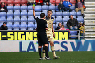 Scott Wootton of Leeds United receives a yellow card from referee Geoff Eltringham. Skybet football league championship match , Wigan Athletic v Leeds Utd at the DW Stadium in Wigan, Lancs on Saturday 7th March 2014.<br /> pic by Chris Stading, Andrew Orchard sports photography.
