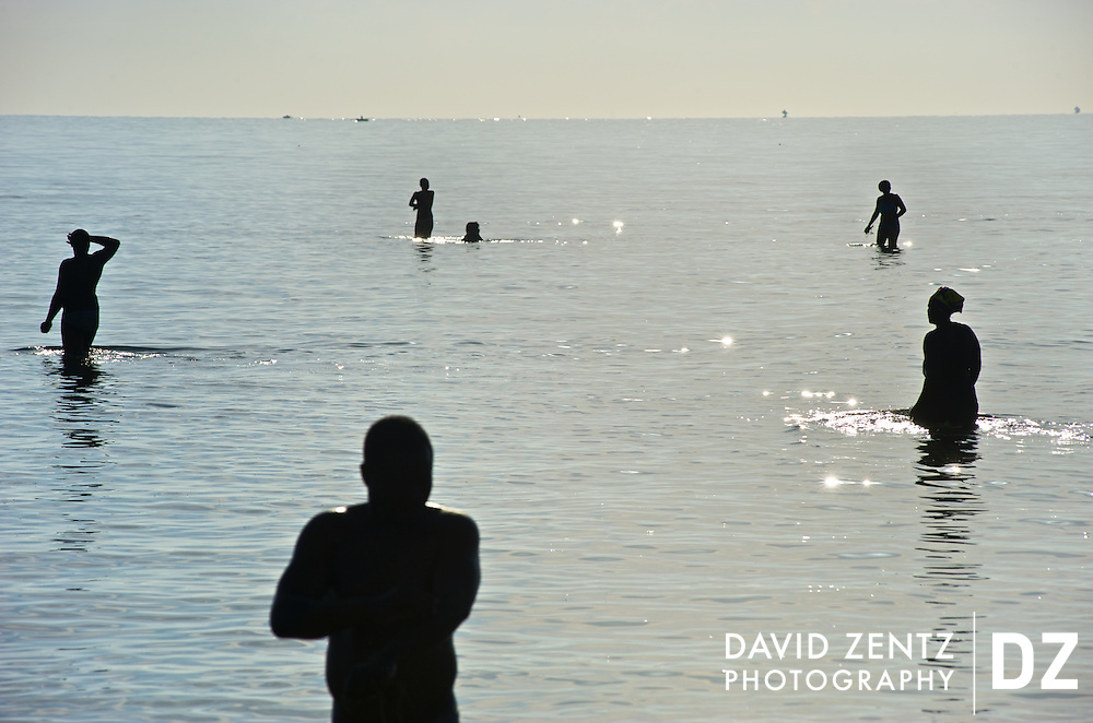 Pilgrims cleanse themselves in the sea during a sunrise voodou ritual at Bord de Mer de Limonade, on the north coast of Haiti on July 25, 2008. After renewing their faith in the mud pit at Plaine du Nord on the days prior, pilgrims migrate to the nearby water, their faith renewed.