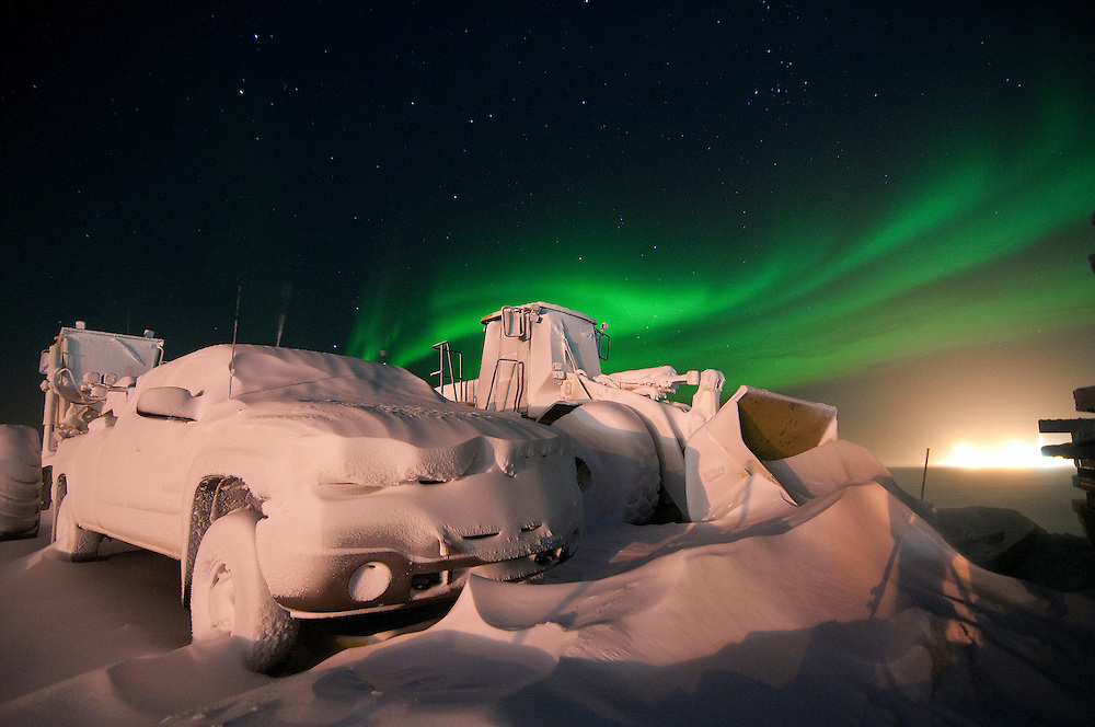The northern lights dance over the skies at Alpine Oilfield as stored equipment awaits dethawing.
