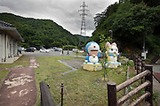 Japanese mountainous rural landscape with two animation figure statues Doraemon and Hello Kitty