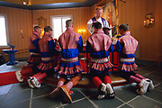 Sami boys in traditional costume kneel while  a priest bless them at their confirmation ceremony in the church of Kautokeino, Norway. The Sami living in Kautokeino hold confirmations and other life cycle ceremonies at Easter time, after which the reindeer herders move with their herds to the Atlantic coast for summer pasture. The traditional tunics are made of wool and the winter shoes and trousers of reindeer fur. The belts have silver decorations.
