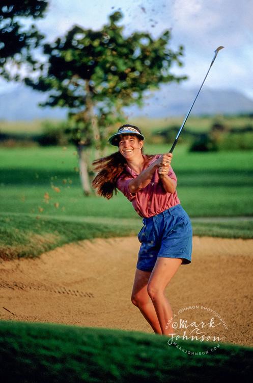 Woman golfer in sand trap - Kauai, HI