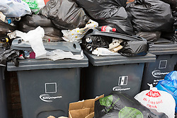 © Licensed to London News Pictures. 25/05/2015. London, UK. Overflowing rubbish bins at the back of residential properties in Dagenham, east London. The GMB union has been on strike since 13th May which is due to end today, on bank holiday Monday. Further strike action is planned in Barking and Dagenham.  Photo credit : Vickie Flores/LNP