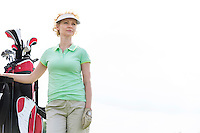 Low angle view of confident female golfer standing against clear sky