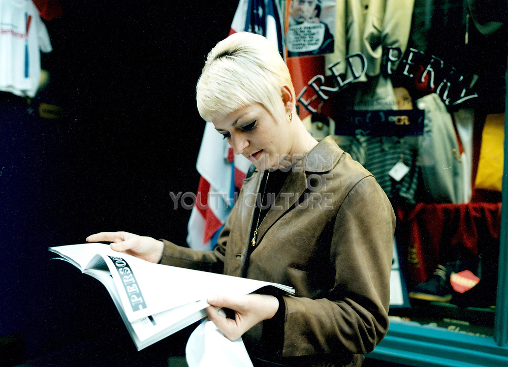 Young woman reading the newspaper in front of Fred Perry shop front.