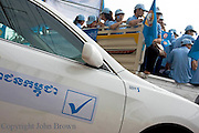 A modern car is parked on a city sidewalk during a campaign rally for the rulling Cambodia People's Party (CPP) in Kampong Cham, Cambodia.