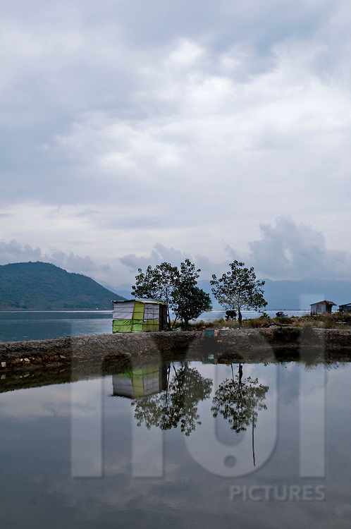 Landscape of a pond with a shack covered with tarpaulin. Seascape in background. Khanh Hoa area, Vietnam, Asia