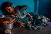 Poonam's older sister Jyoti, 14, is playing with a bowl of fresh rice while lying on the floor of her family's newly built home in Oriya Basti, one of the water-contaminated colonies in Bhopal, central India, near the abandoned Union Carbide (now DOW Chemical) industrial complex, site of the infamous '1984 Gas Disaster'.