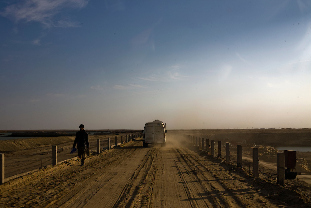CREDIT: DOMINIC BRACCO II..SLUG:PRJ/KAZAKHSTAN..DATE:10/30/09..CAPTION:A man walks down the road near the Syr Darya river on October 30, 2009 near Aralsk, Kazakhstan...Aral Sea Overview: ..During the 1960s the USSR began irrigating the waters of the Aral Sea in southern Kazakhstan to combat their growing food crisis. The Soviets severely miscalculated and water began receding quickly from the port cities. The waters continued to recede. By 2000 the water was 80 km away from the city of Aralsk, a main seaport in Kazakhstan. In 2005 with help from the World Bank, construction began on a 13km dike that locals hoped would bring the waters back to their original shores. The project raised water quality and fishing was able to resume, however four years after completion of the dike the water is still 50km from Aralsk's port. Locals seem mixed on the possibility of the sea returning after more than 40 years without the sea. Fishermen from Aralsk make a three-hour path through soft desert road along the former seabed. The only source of income for many is cattle, horses, and camels, which have, began to overgraze the areas of the former seabed and surrounding desert. Because of this nutrient rich topsoil is lifted by the wind and the process of desertification continues.  .