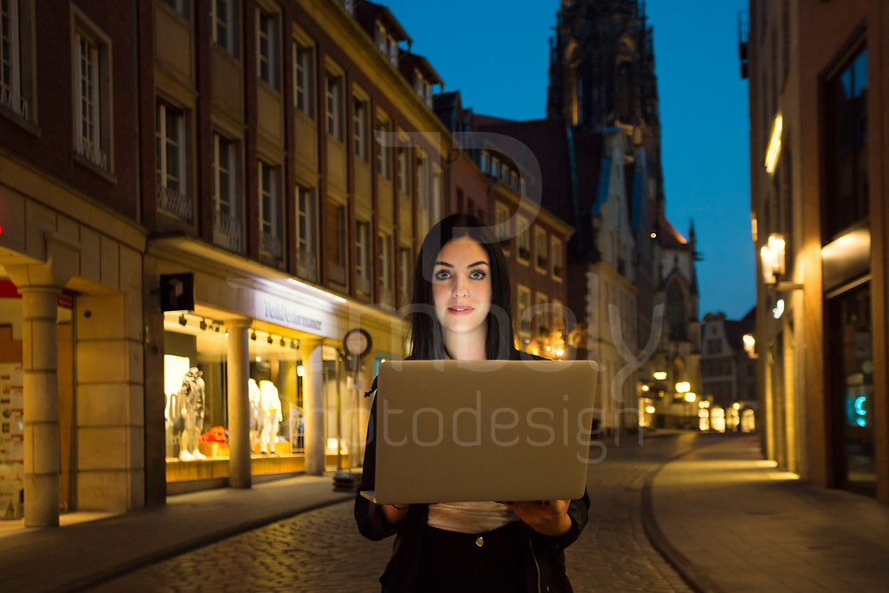 young girl in muenster old city at night with laptop