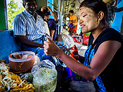 25 NOVEMBER 2017 - YANGON, MYANMAR: A snack vendor prepares an order for a customer on the Yangon Circular Train. The Yangon Circular Train is a 45.9-kilometre (28.5 mi) 39-station two track loop system connects satellite towns and suburban areas to downtown. The train was built during the British colonial period, the second track was built in 1954. Trains currently run both directions (clockwise and counter-clockwise) around the city. The trains are the least expensive way to get across Yangon and they are very popular with Yangon's working class. About 100,000 people ride the train every day. A a ticket costs 200 Kyat (about .17¢ US) for the entire 28.5 mile loop.    PHOTO BY JACK KURTZ
