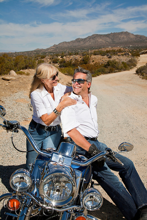 Senior couple sitting on motorcycle and smiling at each other