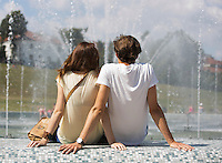 Rear view of couple sitting on fountain wall