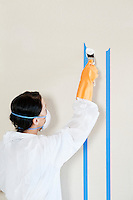 Rear view of a female worker in protective clothing painting wall