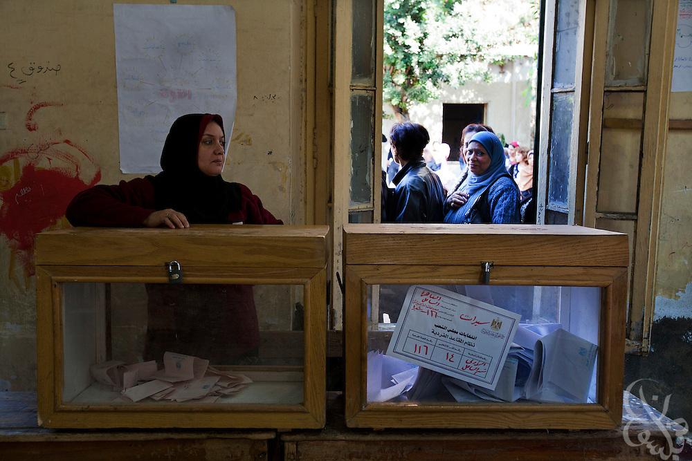 A Egyptian election worker stands behind a ballot box during the first round of historic free parliamentary elections Nov 28, 2011 at a polling station in the Shubra district of the capital, Cairo. The first round of voting (1 of three) for the election, the first since the revolution in Egypt that ousted former president Hosni Mubarak earlier in the year, saw very high voter turnout and is hoped to be a positive step in the direction of a new democratic spirit for the country. (Photo by Scott Nelson)