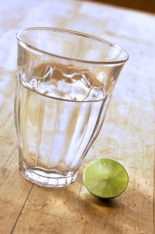 Glass of water with lime on wood table