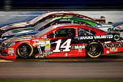 Jul 6, 2013; Daytona Beach, FL, USA; NASCAR Sprint Cup Series driver Tony Stewart (14), David Stremme (30) and Juan Pablo Montoya (42) battle for position on the backstretch during the Coke Zero 400 at Daytona International Speedway.