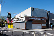 Brooklyn, NY - 15 April 2020. Even Starbucks, on Hillel Place near Brooklyn College, is shuttered for now, its flag still flying over the pedestrian street. Stores and restaurants near Brooklyn College in Brooklyn's Midwood Neighborhood close in response to orders for non-essential businesses to close. Some food businesses tried to remain open for takeout, but could not afford to, especially after the college closed.